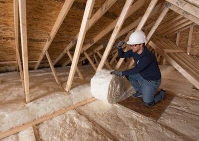 Austin Company | installing white fiberglass insulation in attic of residential home