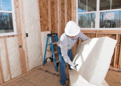 Austin Company | installing white fiberglass insulation in home