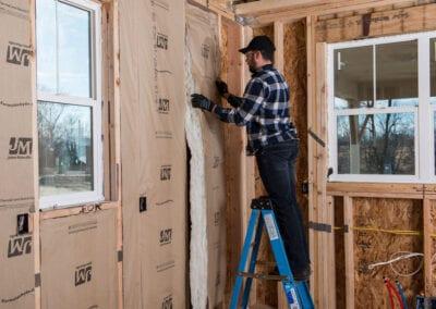 Austin Company | installing fiberglass insulation in walls of home