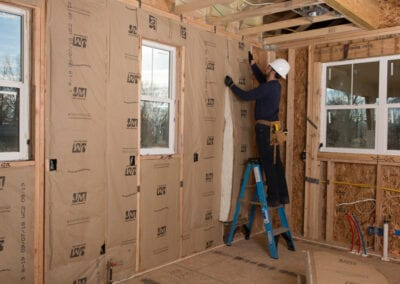 Austin Company | worker installing white fiberglass in walls of home addition